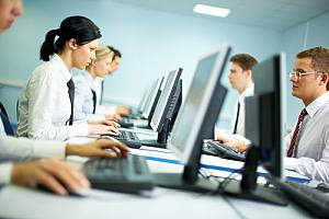 Employees using computer with financial info on hardware