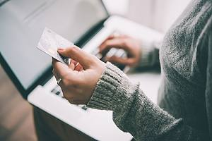 Woman using credit card on laptop