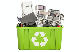 green recycling bin full of old electronics to recycle